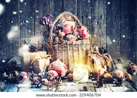 Christmas Gifts. Basket, Burning Candle, red balls, pine cones, snowflakes on Wooden Background. Vintage style with Drawn Snowfall - stock photo