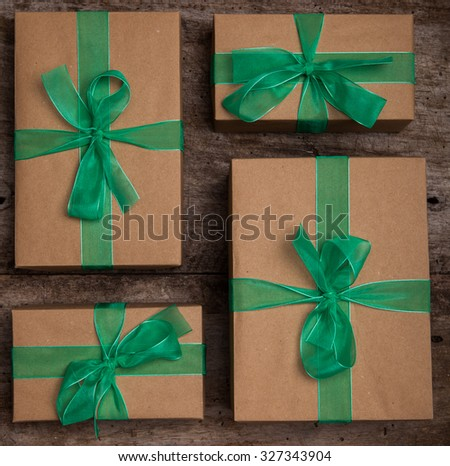 Christmas gifts box presents with brown paper and green ribbon - stock photo