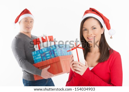 Christmas gifts. Cheerful young couple in Santa hat holding the gift boxes and smiling while standing isolated on white