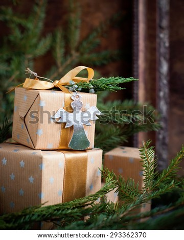 Christmas Gifts Decorated with Cardboard Angel, Ribbon and Natural Cypress  on Holiday Vintage Background - stock photo