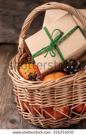 Christmas gifts, tangerines and cones in a basket - stock photo