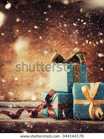 Christmas Gifts under the Snowfall. Festive Boxes in Blue Paper with Different Color Bows on Wooden Background. Toned and Drawn Snow - stock photo
