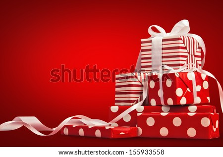 Christmas gifts with ribbon on a red background - stock photo