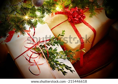 Christmas gifts with ribbons and bows under the tree - stock photo