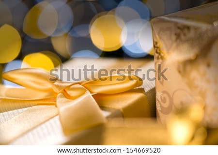 Christmas Gifts wrapped in golden paper and ribbon - stock photo