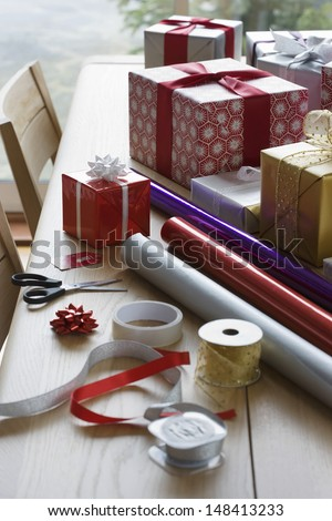 Christmas Gifts; Wrapping Paper And Accessories On Dining Table