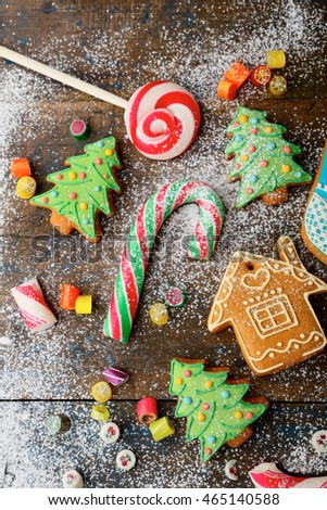 Christmas ginger cookies, cane, lollipop and sweet candy strewn with snow on wooden background