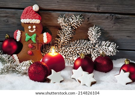 Christmas gingerbread bear christmas bulbs cinnnamon stars pine twig candle on pile of snow against wooden wall - stock photo