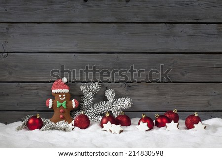 Christmas gingerbread bear christmas bulbs cinnnamon stars pine twig on pile of snow against wooden wall - stock photo