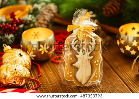 Christmas gingerbread cookies deer on rustic background with Christmas decorations and candle. Shallow focus