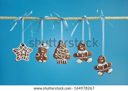 Christmas gingerbread cookies of various shapes hanging on a ribbon on a blue background.