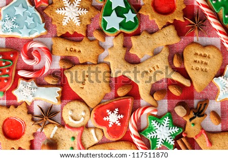 Christmas gingerbread cookies over tablecloth - stock photo