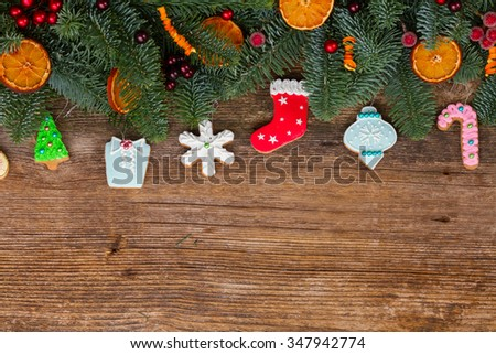 christmas gingerbread cookies with fir tree border on wooden background  - stock photo