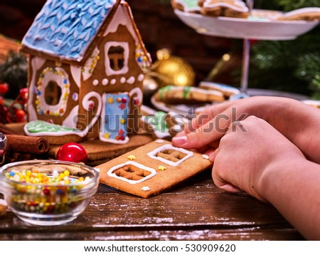 Christmas gingerbread house. Hands close-up child. Christmas still life, biscuits. Small edible beads for decorating cakes. Child development.
