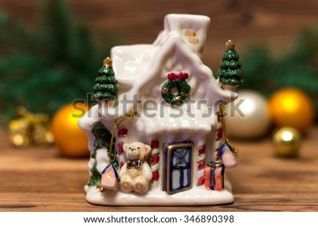 Christmas gingerbread house near the fir branches and Christmas balls on a wooden background - stock photo
