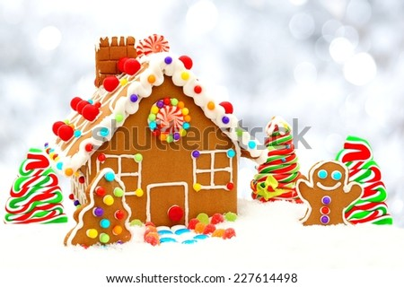 Christmas gingerbread house scene with twinkling silver light background - stock photo