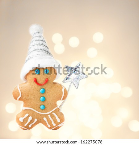 Christmas Gingerbread Man Cookie with Santa hat  on sparkling festive background with copyspace for text, closeup. - stock photo