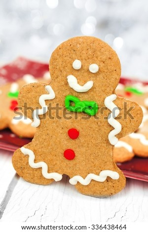 Christmas gingerbread man standing with plate of cookies in background against white wood