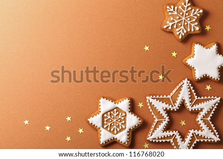 Christmas gingerbreads with golden stars on brown paper background. Top view - stock photo