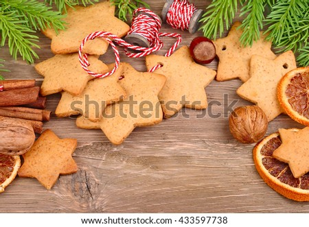 Christmas gingersnap on a string, dried oranges and nuts on a wooden background. A Christmas background with space for the text.