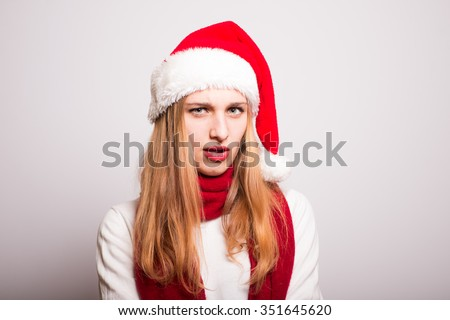 Christmas girl alarmed. Santa hat isolated portrait of a woman on a gray background.