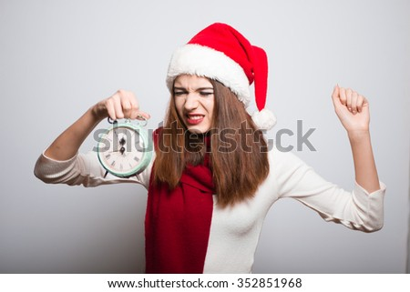 Christmas girl angry at the alarm clock. Santa hat isolated portrait of a woman on a gray background. - stock photo