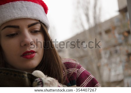 Christmas girl drinking tea to keep warm in winter. Santa hat isolated portrait of a woman on a gray background.