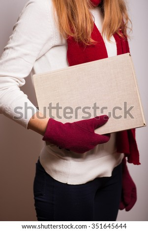 Christmas girl goes somewhere with a book. Santa hat isolated portrait of a woman on a gray background. - stock photo