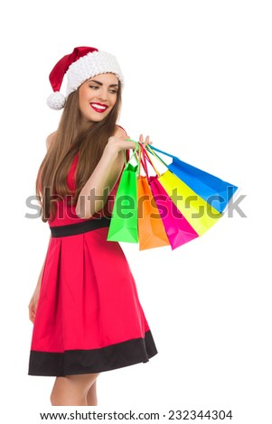 Christmas girl holding colorful shopping bags and looking over shoulder. Three quarter length studio shot isolated on white.