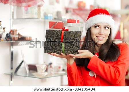 Christmas Girl Holding Presents in Gift Shop - Beautiful smiling woman holding a pile of wrapped Christmas gifts  - stock photo