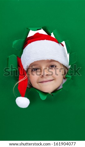 Christmas girl looking through hole in green cardboard paper