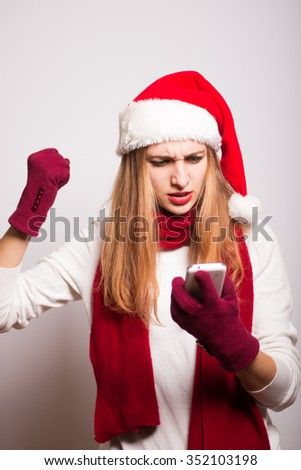 Christmas girl looks at the phone waiting. Santa hat isolated portrait of a woman on a gray background. - stock photo