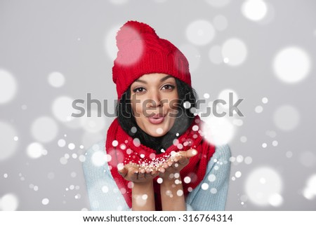 Christmas Girl. Mixed race african american - caucasian woman wearing knitted warm scarf and hat blowing snow at you, looking at camera, over gray background - stock photo