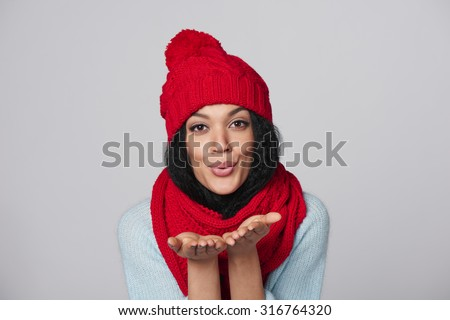 Christmas Girl. Mixed race african american - caucasian woman wearing knitted warm scarf and hat blowing a kiss, looking at camera, over gray background - stock photo
