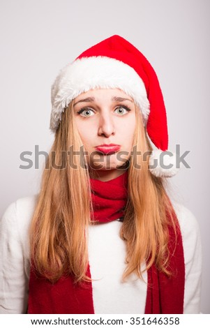 Christmas girl offended. Santa hat isolated portrait of a woman on a gray background. - stock photo