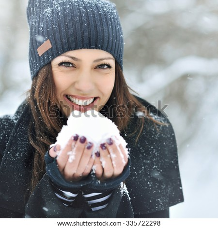 Christmas girl outdoor portrait. Winter woman blowing snow in a park