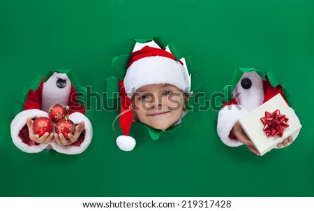 Christmas girl peeking out from hole in wrapping paper - funny holidays theme - stock photo