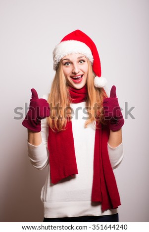 Christmas girl showing a thumbs up gesture. Cool! Santa hat isolated portrait of a woman on a gray background. - stock photo