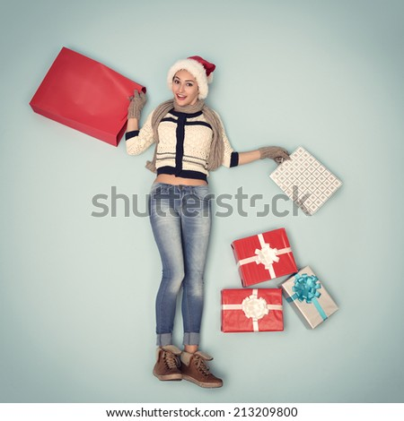 Christmas girl with gift and shopping bags in santa's hat, image toned - stock photo