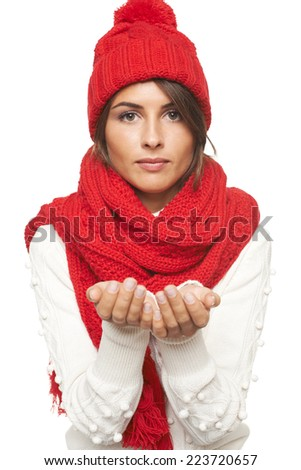Christmas Girl. Woman wearing knitted warm red scarf and hat holding blank empty copy space for your product in her palms, over white background