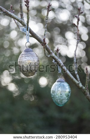 Christmas glass decoration hanging outside on the branch of a tree. Back lighting has caused a bokeh effect behind the bauble. - stock photo