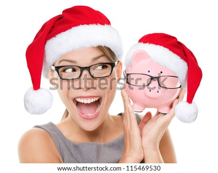 Christmas glasses eyewear sale concept. Woman wearing eye glasses and santa hat is holding piggy bank with glasses. Excited multiracial young woman isolated on white background. - stock photo
