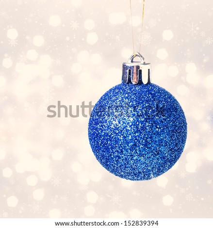 Christmas glittering blue bauble hanging  over Defocused Christmas Bokeh bright background - stock photo