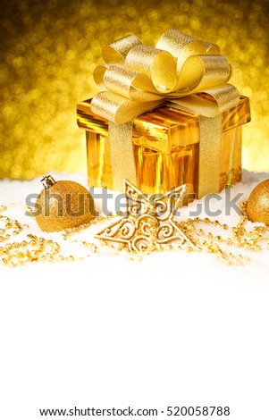 Christmas gold gift box with balls and star on snow. New Year Decorations