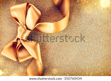 Christmas Golden Ribbon Bow on a Blinking Holiday Background. Greeting Card with copy space for your text. Beautiful Gold Christmas Gift Border art design - stock photo