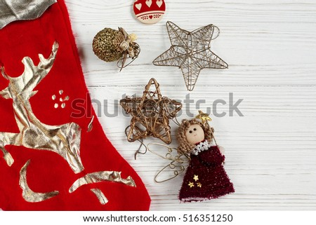 christmas golden toys and red stockings on white rustic wooden background. space for text. holiday greeting card concept. unusual creative view