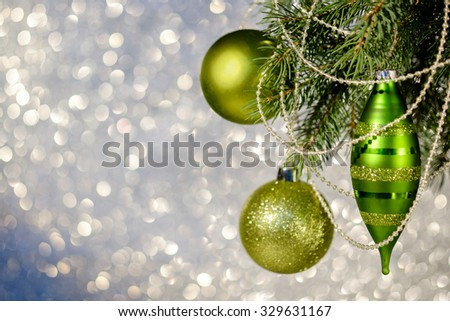 Christmas green balls on a Christmas tree branch over blurred shiny background. Space for text.