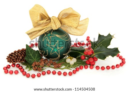 Christmas green sparkling bauble with bow surrounded by holly, mistletoe, ivy and cedar leaf sprigs with gold pine cones and red bead chain over white background. - stock photo