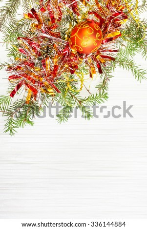 Christmas greeting card - border from one orange Xmas ball and tree branch on blank paper background - stock photo