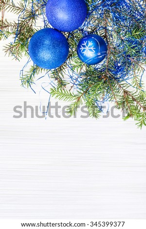 Christmas greeting card - border from three blue Xmas balls and tree branch on blank paper background
